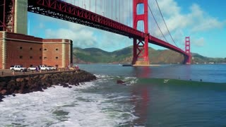 Aerial view of surfers riding waves under Golden Gate Bridge 2