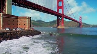 Aerial view of surfers riding waves under Golden Gate Bridge 2