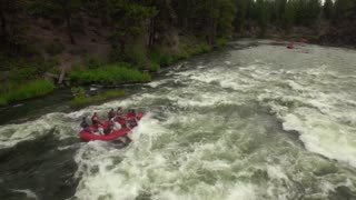 Aerial view of whitewater rafting next to forest 6