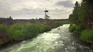 Aerial view of whitewater rafting next to forest