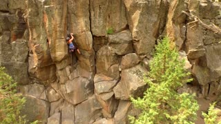 Aerial view of woman rock climbing a mountain 3