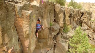 Aerial view of woman rock climbing a mountain 4
