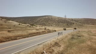 Bicycle race on open road surrounded by mountains and blue sky 2