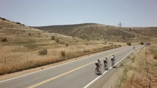 Bicycle race on open road surrounded by mountains and blue sky 4
