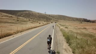 Bicycle race on open road surrounded by mountains and blue sky 5