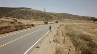 Bicycle race on open road surrounded by mountains and blue sky 6