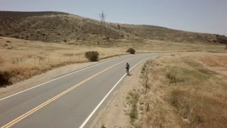 Bicycle race on open road surrounded by mountains and blue sky 7