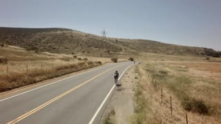 Bicycle race on open road surrounded by mountains and blue sky 8