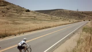 Bicycle race on open road surrounded by mountains and blue sky