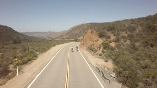 Bicyclists race down road between large mountains 2