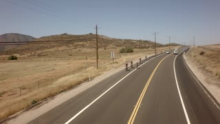 Bicyclists race down road between large mountains 4