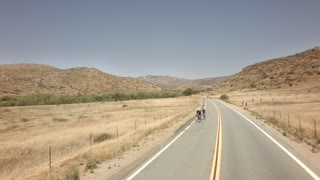 Bicyclists race down road between large mountains 5