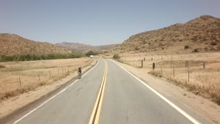 Bicyclists race down road between large mountains 6