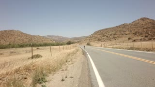 Bicyclists race down road between large mountains 8
