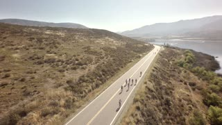Bike race next to large mountains and river 2