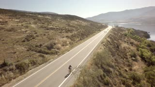 Bike race next to large mountains and river 3