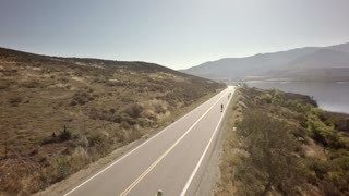 Bike race next to large mountains and river