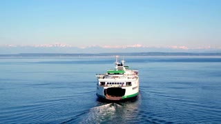 Boat crosses water towards Seattle mountains under blue sky 3