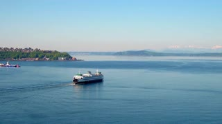 Boat crosses water towards Seattle mountains under blue sky 4
