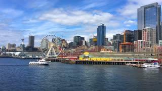 Boat travels toward Seattle skyline and ferris wheel