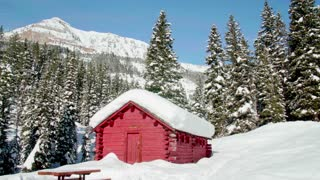 Close up of log cabin in the winter with snow covered mountains in the background