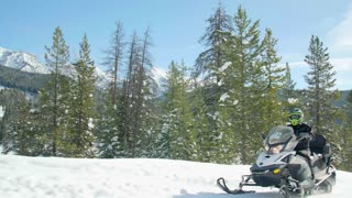 Close up of snowmobile driving through the forest 2