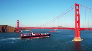 Container ship travels under Golden Gate Bridge by mountains 3