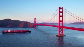Container ship travels under Golden Gate bridge by mountains 4