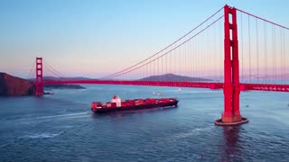 Container ship travels under Golden Gate bridge by mountains 5