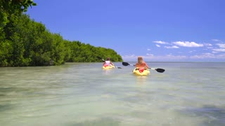 Couple kayaking on clear ocean sunny day by tropical island 3