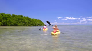 Couple kayaking on clear ocean sunny day by tropical island 4