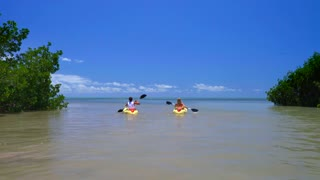 Couple kayaking on clear ocean sunny day by tropical island 6