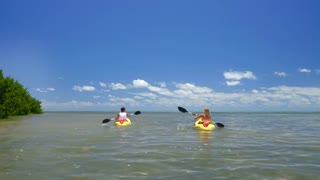 Couple kayaking on clear ocean sunny day by tropical island 7