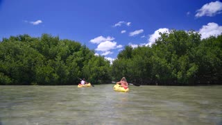 Couple kayaking on clear ocean sunny day by tropical island 8