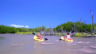 Couple kayaking on clear ocean sunny day by tropical island 9
