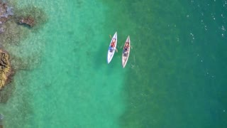 Couple Kayaks Near Rocks in Tropical Blue Water from Aerial Drone