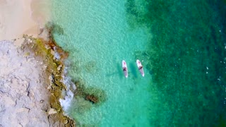 Couple Paddle Boarding Near Rocks in Tropical Blue Water from Aerial Drone 3