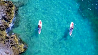 Couple Paddle Boarding Near Rocks in Tropical Blue Water from Aerial Drone