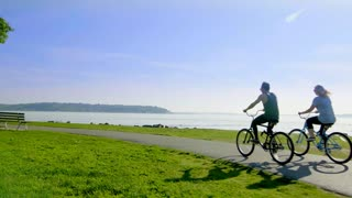 Couple rides bikes by Seattle waterfront 2