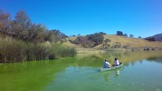 Couple rides canoe across lake on sunny day 2