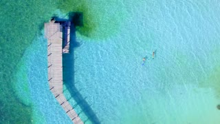 Couple Snoreling in Tropical Clear Blue Water Near Dock from Aerial Drone 2