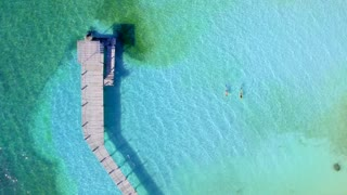 Couple Snoreling in Tropical Clear Blue Water Near Dock from Aerial Drone 3