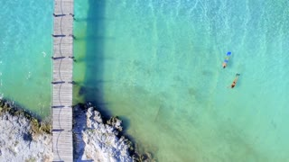 Couple Snoreling in Tropical Clear Blue Water Near Dock from Aerial Drone 5