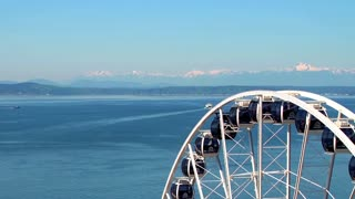 Drone close up of ferris wheel by Seattle river and mountains