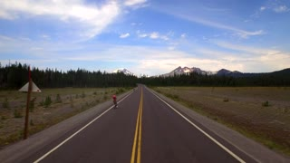 Drone shot of bicycle riders by mountainside under blue sky 2