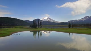 Drone shot of large lake by green trees and snow capped mountains 2