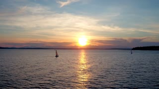Drone video of sailboat crossing water during sunset 2