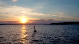 Drone video of sailboat crossing water during sunset 3