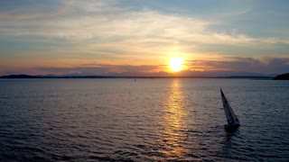 Drone video of sailboat crossing water during sunset 4