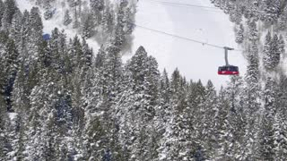 Drone video of ski lift traveling above snow covered trees 3